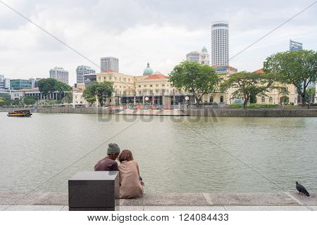 Singapore - Mar 26 2016: In late afternoon a young couple were sitting closely at waterfront of Raffles Place facing Singapore River and Asian Civilisations Museum with a pideon resting 2 meters away.