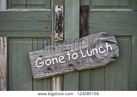 Gone to lunch sign on old green doors.
