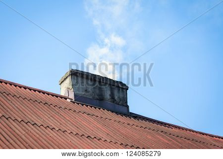Smoke flying over chimney of countryside house on blue sky background.