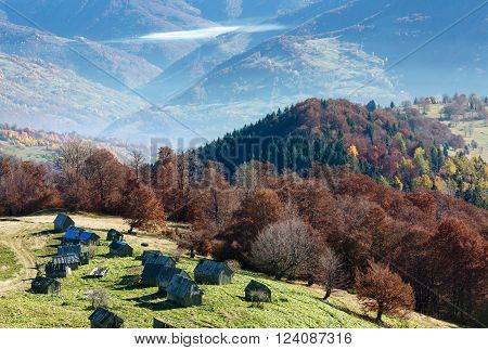 Morning fog in autumn Carpathian and wooden barns on slope.
