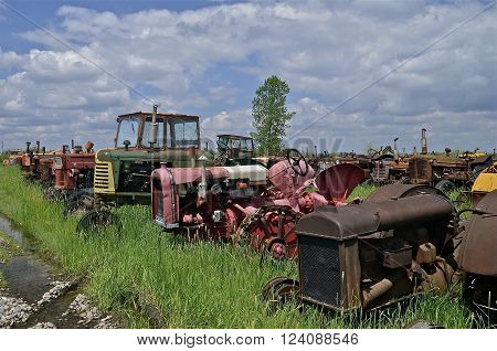 Many old tractors of various colors  are parked in rows in a junk and salvage yard.