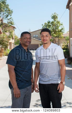 Multiracial teenage son taller than his dad.