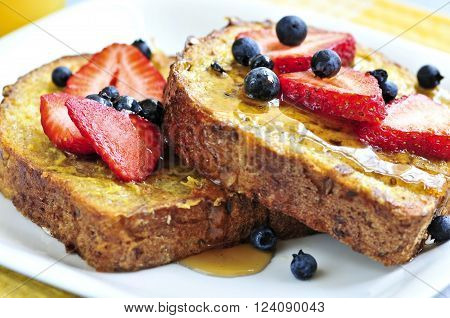 Breakfast of french toast with fresh berries and maple syrup