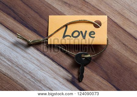 concept for a happy loving life using an old decorative key and a hand written tag attached by a golden cord