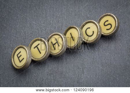 ethics word in old typewriter keys against gray slate stone