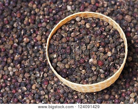 Black peppercorn background. Dried black pepper in weave bowl. Pepper seed.