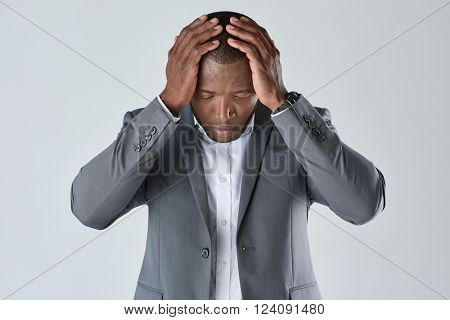 Black african business man feeling stress, having a headache migraine, facing deadline in studio