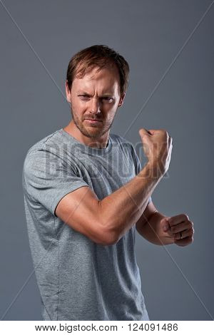 Caucasian man flexing his strong muscular biceps in studio, healthy wellness lifestyle