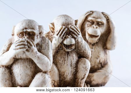 close up of hand small statues with the concept of see no evil, hear no evil and speak no evil.