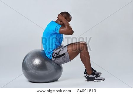 Fit healthy man uses pilates gym fitness ball as part of toning and core muscle building training exercises