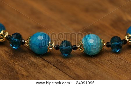 A string of jewelry on a wooden background