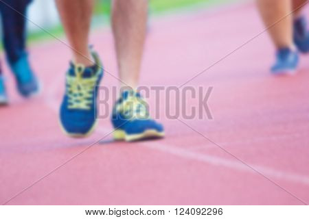 blur image young fitness men legs running at stadium