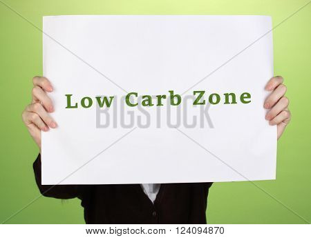 Woman holding paper with Low-Carb Zone text on color background