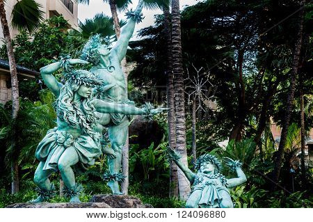 Waikiki, Honolulu, Hawaii, USA - December 13, 2015: Bronze Hawaiian dancers frozen in action with powerful poses outside the Hilton Hawaiian Village. This area is open to the public and is next to the Ala Moana Boulevard thoroughfare.