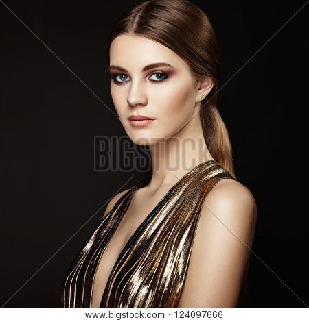 Fashion portrain of young beautiful woman in gold dress. Brunette glamour lady with perfect make up and hairstyle
