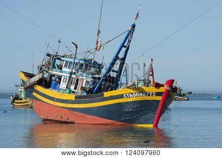 MUI NE, VIETNAM - DECEMBER 25, 2015: Fishing schooner preparing to go to sea. In the fishing harbour of Mui Ne