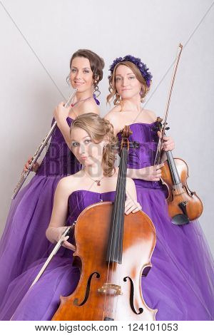 musical trio with instruments in purple dresses