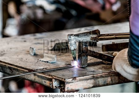 HDR image of a technician using welder in factory's workshop