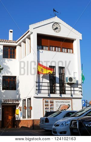 COMARES, SPAIN - JUNE 29, 2008 - Town Hall with clock and a Spanish flag in the town square Comares Axarquia region Malaga Province Andalucia Spain Western Europe, June 29, 2008.