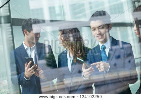 Group of business people discuss somehting on cellphone