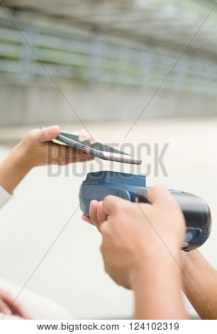 Woman using mobile phone for paying the bill