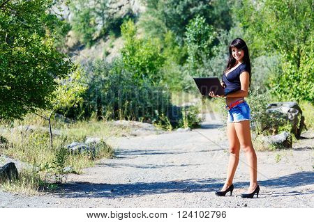 beautiful smiling brunette woman working with a laptop among the greenery and stones. Student or businesswoman ** Note: Visible grain at 100%, best at smaller sizes