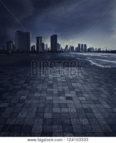 An empty scene of a stone tile floor and skyline of Chao Praya river with a dark stormy sky