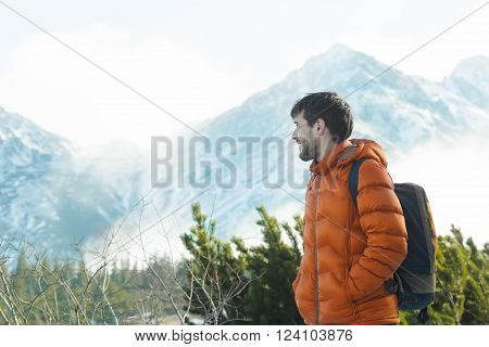 Profile of smiling mountaineer is looking at astonishing snowy summits view