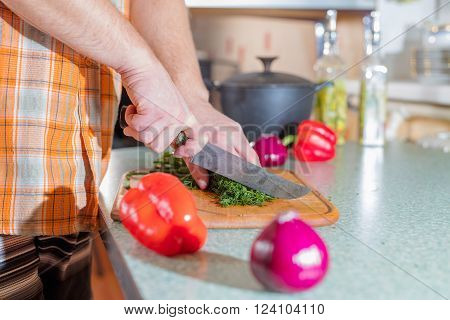 Man's hands cutting greenery and vegetables by knife