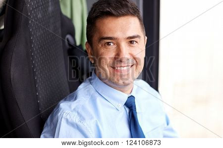 transport, tourism, business trip and people concept - close up of happy bus driver or businessman in shirt and tie