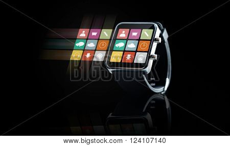 modern technology, application, object and media concept - close up of black smart watch with app icons on screen over black background