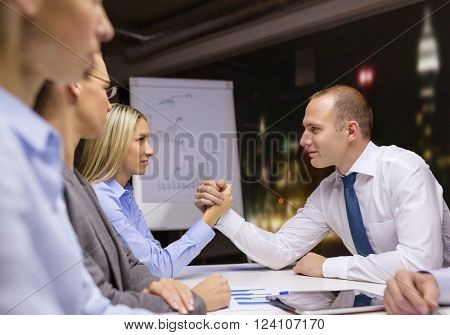 business and office concept - businesswoman and businessman arm wrestling during meeting in office