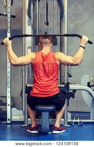 sport, fitness, bodybuilding, lifestyle and people concept - man exercising and flexing muscles on cable machine in gym