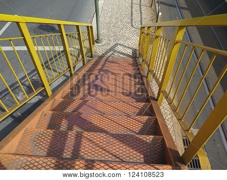 Yellow Steel stairs and railing leading down from road and rail overpass