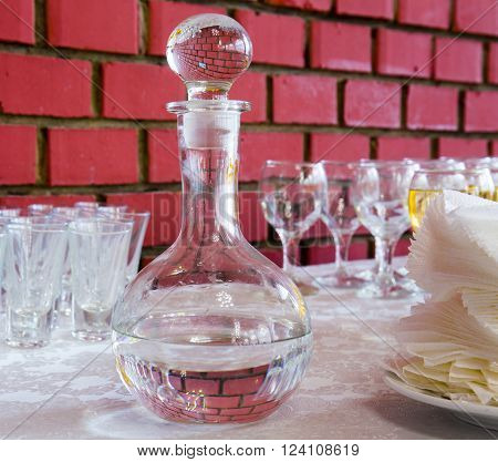Carafe with vodka on red brick wall background