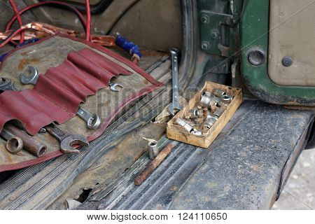 Open car boot with various tools next to a rusty metal bumper angled shot with selective focus