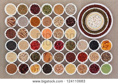 Large dried health food sampler in china bowls forming an abstract background over hessian. High in antioxidants, vitamins, minerals and dietary fibre.