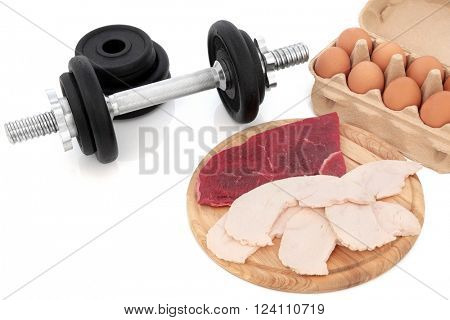 Dumbbell weights with high protein body building health food of chicken, lean steak and eggs.