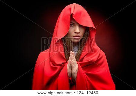 beautiful woman with red cloak praying
