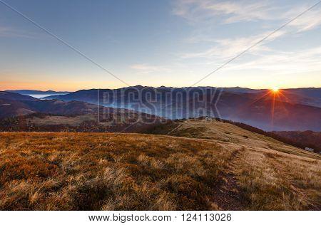 First beams of rising sun in autumn Carpathian. Mountain top daybreak landscape.