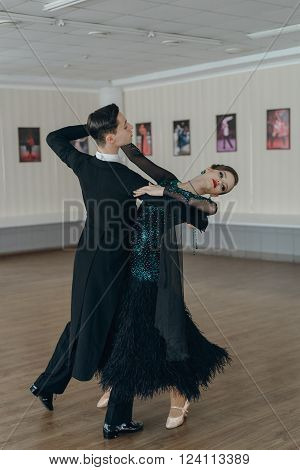 Professional dancers dancing in ballroom. Young couple