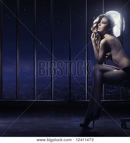 Naked brunette beauty posing at full moon