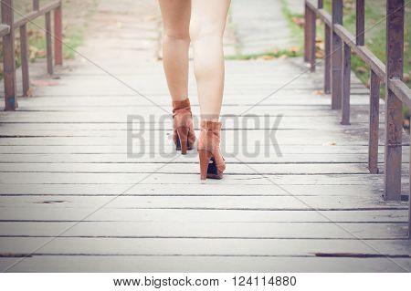 Woman's legs in high heels walking away from the bridge in outdoor scene