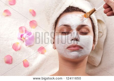 Young woman getting mud mask at spa-salon.