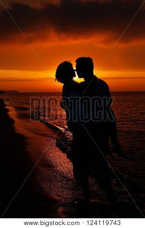 a silhouette of couple in love at sunset