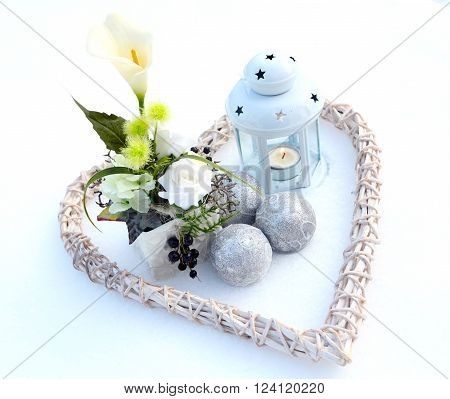 a lantern with Christmas baubles, heart and lantern in the snow