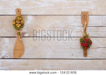 Wooden background with decorative kitchen utencils and empty center