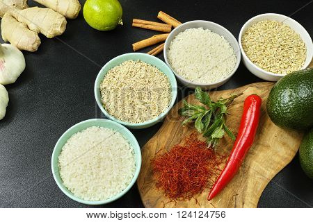 Four bowls with different types of rice: wild rice white basmati rice brown rice and indian spices on olive wood board and black background