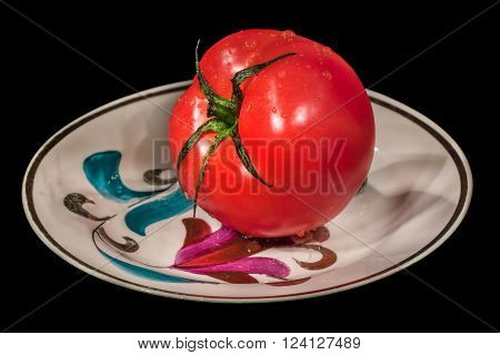 red tomato on a saucer on a black background