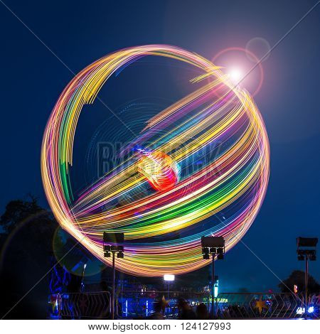 A long exposure photograph of a spinning fairground ride